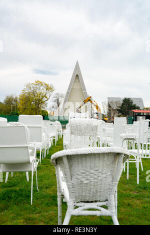 CHRISTCHURCH, NEW ZEALAND - OCTOBER 10 2018; 185 empty white chairs of remembrance with symbols of change in earthmoving machine and  Transitional Ang - Stock Photo