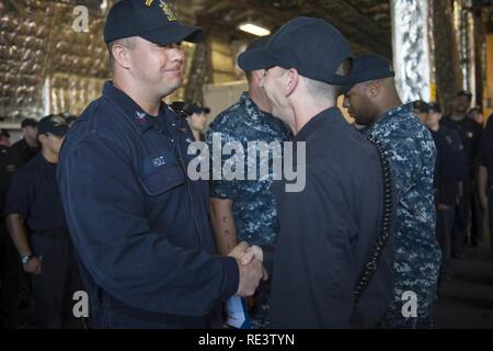 CHANGI NAVAL BASE, Singapore (November 17, 2016) Petty Officer 2nd Class Thomas Scarborough, right, pins Petty Officer 1st Class Walter Holt, left, with the Enlisted Aviation Warfare Specialist (EAWS) device aboard USS Coronado (LCS 4). Holt is one of two sailors to be the first to receive his EAWS aboard an LCS. Currently on a rotational deployment in support of the Asia-Pacific Rebalance, Coronado is a fast and agile warship tailor-made to patrol the region's littorals and work hull-to-hull with partner navies, providing 7th Fleet with the flexible capabilities it needs now and in the future