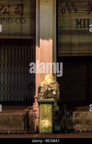 Green wheelie trash bin with bag of trash on top in the street ready for collection. - Stock Photo
