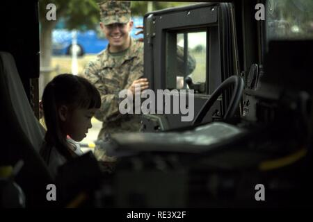 An Okinawa resident sits in a Humvee Nov. 20, 2016 during the Japan Ground Self-Defense Force Festival on Camp Naha, Okinawa, Japan. The festival celebrated the 6th anniversary of the 15th Brigade and the 44th anniversary of Camp Naha. The Humvee was one of three vehicles Marines with Combat Assault Battalion, 3rd Marine Division, III Marine Expeditionary Force brought for display. - Stock Photo