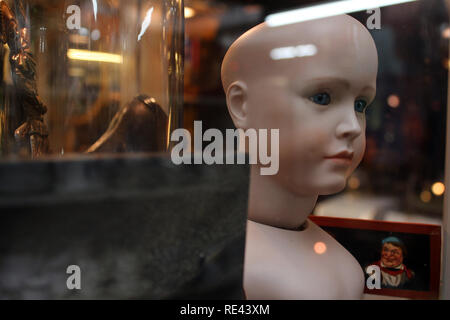 Doll and other objects displayed on a glass cabinet vintage shop en Brighton, England, UK - Stock Photo