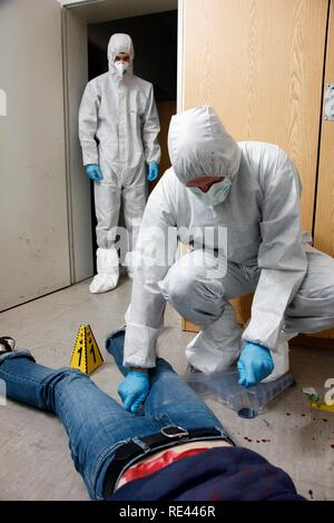 Traces of fibres and micro traces are secured with large duct tape, officers of the C.I.D., the Criminal Investigation - Stock Photo