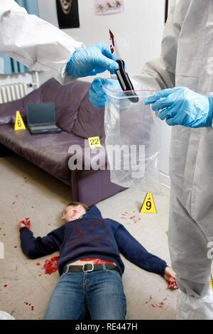 Securing of the possible murder weapon, knife, officers of the C.I.D., the Criminal Investigation Department, gathering forensic - Stock Photo