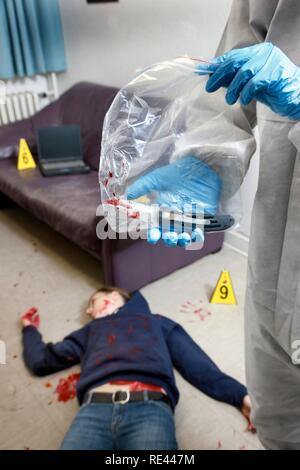 Securing of the possible murder weapon, knife, officer of the C.I.D., the Criminal Investigation Department, gathering forensic - Stock Photo