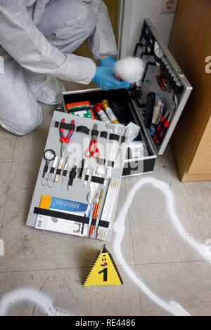 Forensic's case, officer of the C.I.D., the Criminal Investigation Department, gathering forensic evidence at the scene of a - Stock Photo