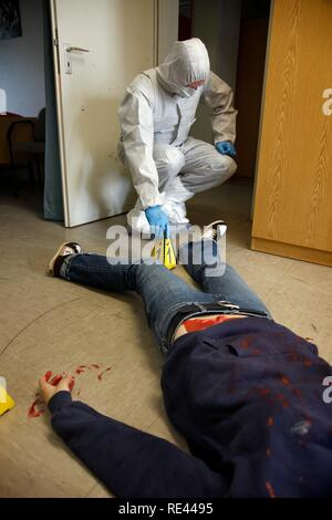Officers of the C.I.D., the Criminal Investigation Department, gathering forensic evidence at a crime scene - Stock Photo