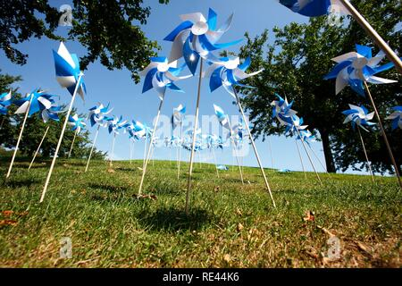 Blue and white plastic wind wheels as decoration on a lawn - Stock Photo