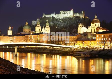 Old town with Kollegienkirche church, the Salzburger Dom cathedral and Festung Hohensalzburg fortress, Salzach river, at night - Stock Photo