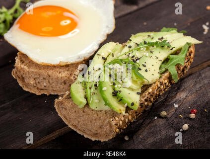 Closeup of two different bruschettas with avocado, rucola sesame, seeds, egg on a wooden table. - Stock Photo
