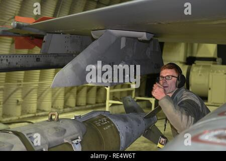 Staff Sgt. Kenneth Gullette, 35th Aircraft Maintenance Unit weapons load crew chief, guides a Joint Direct Attack Munition GBU-31 onto the wing of an F-16 Fighting Falcon at Kunsan Air Base, Republic of Korea, Nov. 30, 2016. Members of the 35th AMU safely prepare F-16's for a variety of missions, which feed into the 8th Fighter Wings priorities of defending the base and being postured to respond to any threats. - Stock Photo