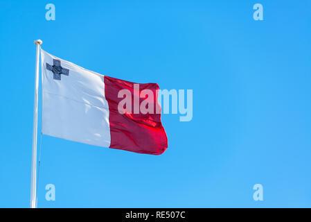 Maltese flag flying in Valletta, Malta against a blue sky - Stock Photo