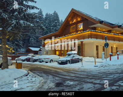 Poiana Brasov, Romania - December 26, 2018: Snowy luxurious guesthouse with Christmas decorations illuminated in the evening in Poiana Brasov, the mos - Stock Photo