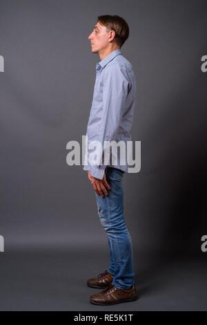 Full length profile view shot of mature handsome Italian man - Stock Photo