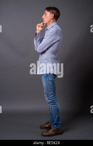 Full length profile view shot of mature handsome Italian man thinking - Stock Photo