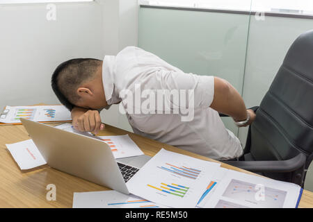Asian businessman touching aching back with pained expression - Stock Photo