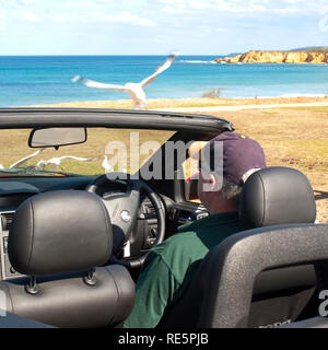 Man sitting in a car watching the beach - Stock Photo
