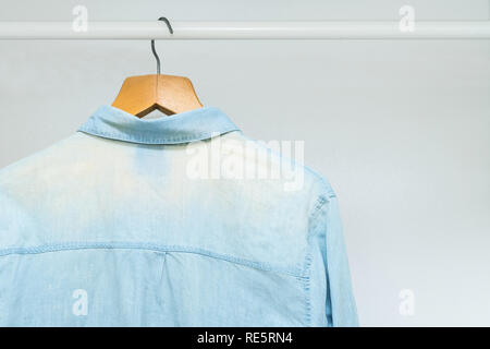 Worn out, bleached out old classic business shirt hanging in a wardrobe - Stock Photo