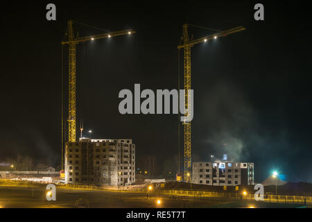 Tower cranes and unfinished multi-storey high near buildings under construction site in night background - Stock Photo