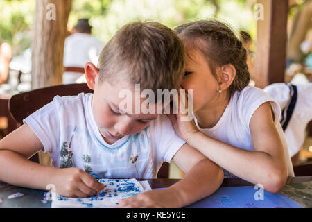 A little boy are whispering something to a pretty girl in a street restaurant. Children's friendship. - Stock Photo