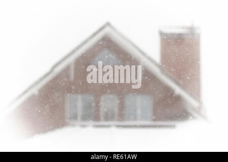 It is snowing outside the window against the background of the neighboring house. - Stock Photo