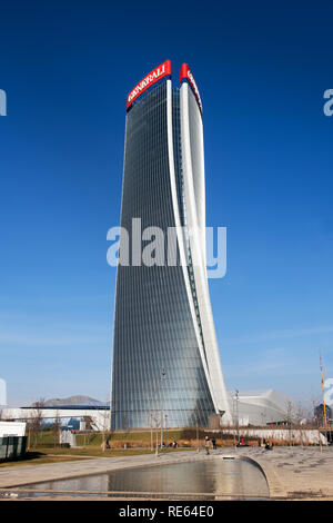 Exterior view of the Generali Tower, Milan with its distinctive warped design by architect Zaha Hadid reflected in a pool below against a blue sky - Stock Photo