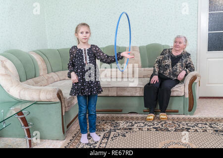 Granddaughter rotates the hoop on the arm, in front of her great-grandmother, sitting on the couch - Stock Photo