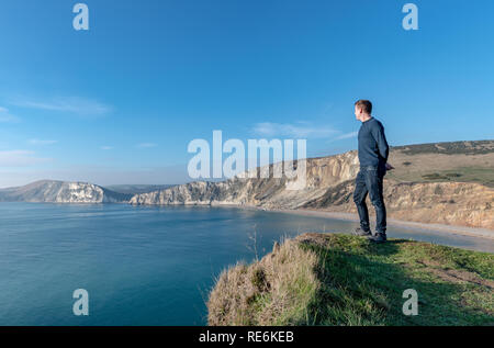 Wareham, UK. Sunday 20th January 2019. A man looks out over Worbarrow Beach on the Jurassic Coast in Dorset. Other people on the beach are wrapped up warm in the 4 degree cold but sunny weather. Credit: Thomas Faull/Alamy Live News - Stock Photo