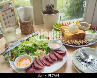 The appetizing honey toast with vanilla ice-cream and fresh fruit served with baked duck salad on wooden table by the window in beautiful cafe - Stock Photo