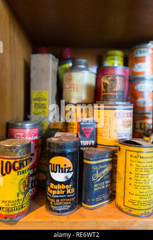 Quebec Province, Canada - 25th January 2015: A stack of old product tins for sale in a flea market, including motor products, paints, household repair - Stock Photo