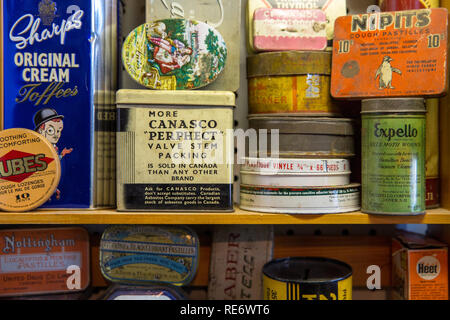 Quebec Province, Canada - 25th January 2015: A stack of old product tins for sale in a flea market, including sweets and medicines. - Stock Photo