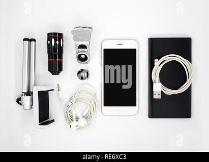Flat lay (Top view) image of accessories (Tripod Phone Holder, Universal Clamp Camera Lens, Earphone, Power Bank, USB Charger Cable) around smartphone - Stock Photo