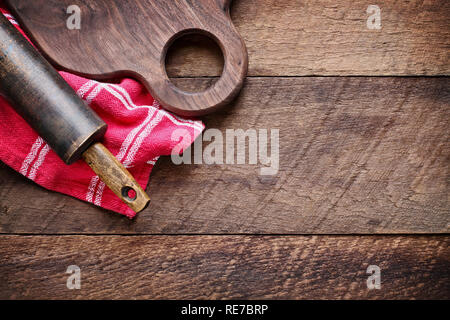 Wooden walnut cutting board and vintage rolling pin over red kitchen towel and rustic old barn wood table. Image shot from above in top view position. - Stock Photo