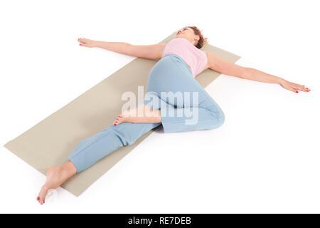 Beautiful Yoga: Reclined Spinal Twist - Real senior woman doing Supta Matsyendrasana exercises - Stock Photo