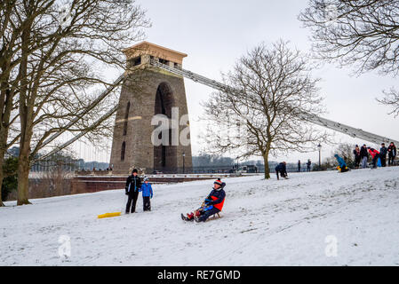 Families enjoying the opportunity of winter snow to sledge down Sion Hill by the Clifton Suspension Bridge Bristol UK - Stock Photo