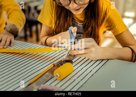 Red-haired girl wearing glasses cutting little yellow ribbon - Stock Photo