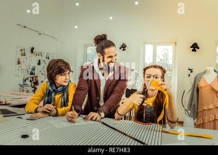 Bearded teacher feeling joyful while working with his students - Stock Photo