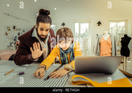 Private tutor in fashion design teaching cute stylish schoolboy - Stock Photo
