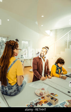 Bearded cheerful fashion designer teaching in his design school - Stock Photo
