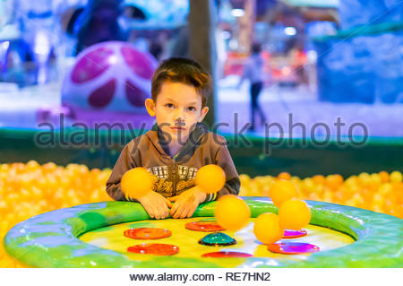 Kownaty, Poland - January 6, 2019: Young boy sitting by a air blowing machine with plastic orange balls on a playground in the Majaland indoor attract - Stock Photo