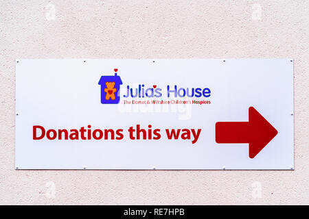 Julias house charity shop donations this way sign - Stock Photo