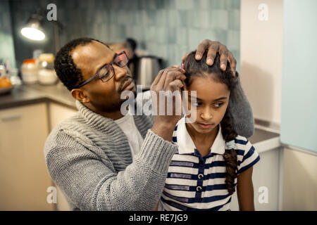 Father wearing grey cardigan fixing hairstyle of his daughter Stock Photo