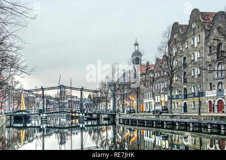 Schiedam, The Netherlands, December 27, 2018: boats, a pedestrian bridge, canal houses, warehouses, a windmill and the harbour church reflect in the w - Stock Photo