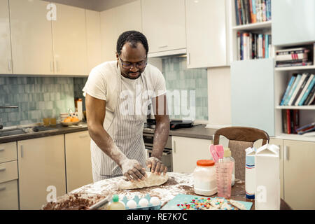 Bearded family man kneading dough while cooking pie - Stock Photo
