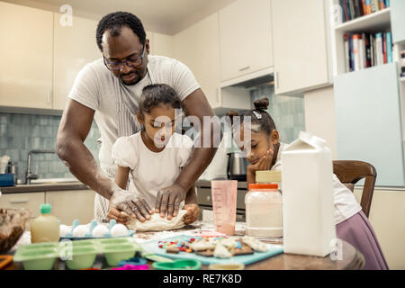 Two daughters feeling involved in watching their father kneading dough - Stock Photo