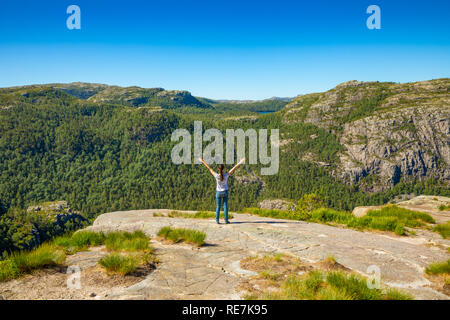 Hiker standing on Preikestolen and looking on the mountain next to Preikestolen in Norway - Stock Photo