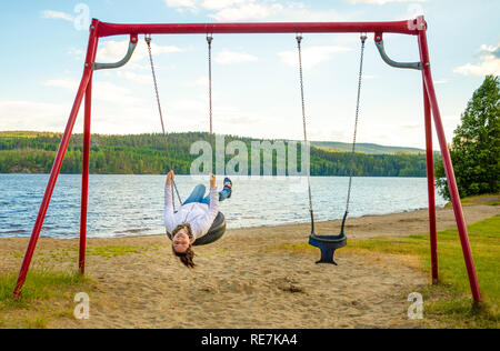 Young woman on swing in Oppstrynsvatn lake in the municipality of Stryn in Sogn og Fjordane county, Norway - Stock Photo