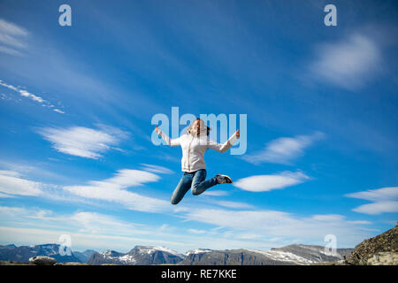 Happy tourist woman over Geirangerfjord and mountains landscape from Dalsnibba viewpoint, Norway - Stock Photo