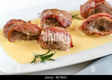 Baked pork tenderloin wrapped in bacon served in a cheese sauce with rosemary - Stock Photo