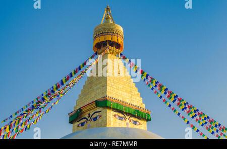The dome and gold spire of Bodhnath Stupa, Kathmandu, Nepal, with Buddhist prayer flags. - Stock Photo