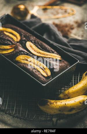 Freshly baked chocolate banana cake with cinnamon in baking tin - Stock Photo